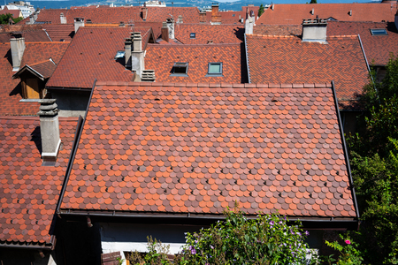 Red flat Alsatian curved tiles roofs houses in Annecy France