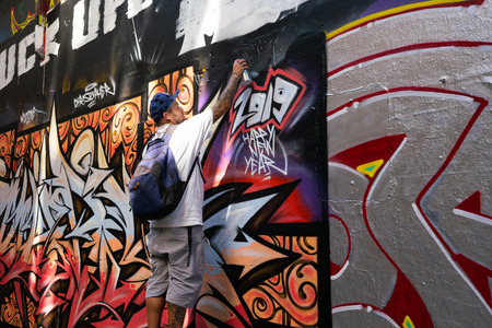 3rd January 2019, Melbourne Australia : street artist in action tagging Happy new year 2019 in Hosier lane in Melbourne Australia