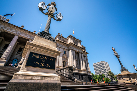 Front view of the Parliament of Victoria with name written on a board and old Victorian street lamp close-up in Melbourne Victoria Australia