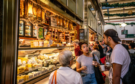 3rd January 2019, Melbourne Victoria Australia : People drinking coffee in front of a cheese shop inside Queen Victoria Market aisle in Melbourne Australia