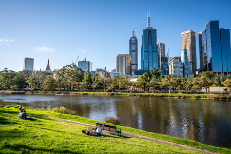 2nd January 2019, Melbourne Australia : People resting on Yarra riverbank promenade grass in central Melbourne and Melbourne CBD skyline in Victoria Australia
