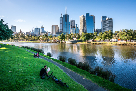 2nd January 2019, Melbourne Australia : Man reading a book on Yarra riverbank promenade grass in central Melbourne and Melbourne CBD skyline in Victoria Australia