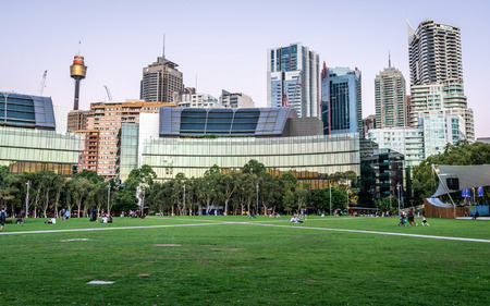 23rd December 2018, Sydney NSW Australia : Grassy place at Tumbalong park at dusk with Sydney skyline in background in Darling Harbour NSW Australia