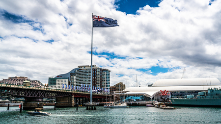 22nd December 2018, Sydney NSW Australia : Sydney Darling Harbour panorama with Giant Australian flag and Pyrmont bridge with overcast weather in NSW Australia