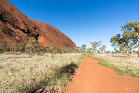 View of red rocks and path of the base walk around Ayers rock in NT outback Australia