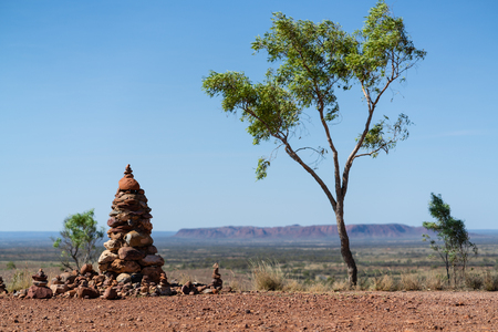 Cairn and gum tree with outback landscape in background in NT outback Australia 写真素材