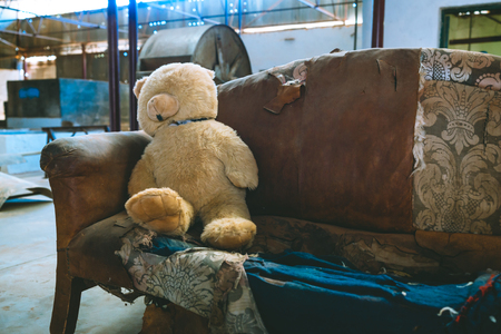 Teddy bear on a vintage sofa in an industrial building : childhood nostalgia concept