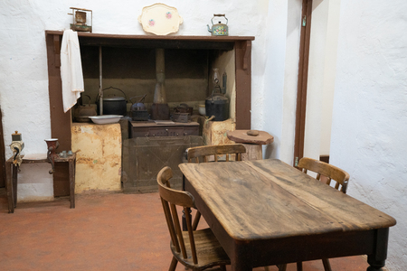 Basic old vintage kitchen with rustic wood table wood-burner and white walls : rudimentary comfort concept