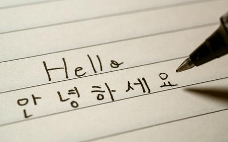 Aprendiz de idioma coreano principiante escribiendo Hola palabra Annyeonghaseyo en caracteres coreanos en un primer plano de un cuaderno Foto de archivo