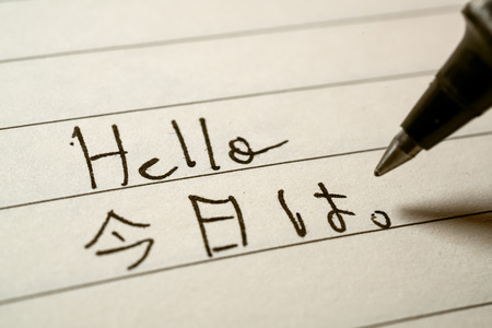 Beginner Japanese language learner writing Hello word in Japanese kanji characters on a notebook close-up shot 写真素材