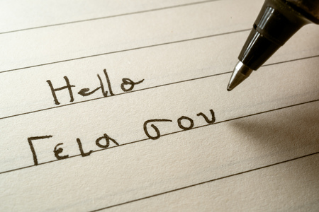 Beginner Greek language learner writing Hello word in greek alphabet on a notebook close-up shot 写真素材 - 123338633