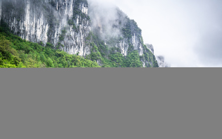 Mufu Grand canyon mountains cliffs in middle of clouds mist and green forest in Enshi Hubei China