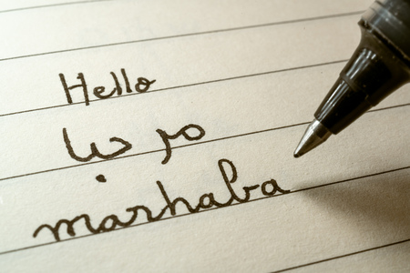 Beginner Arabic language learner writing Hello word Marhaba in abjad Arabic alphabet on a notebook close-up shot 写真素材 - 123338639