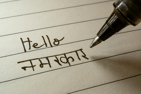 Beginner Hindi language learner writing Hello Namaste word in Indian Hindi alphabet on a notebook close-up shot