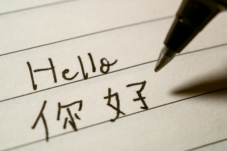 Beginner Chinese language learner writing Hello word in Chinese characters on a notebook macro shot