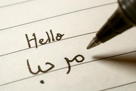 Beginner Arabic language learner writing Hello word in abjad Arabic alphabet on a notebook close-up shot