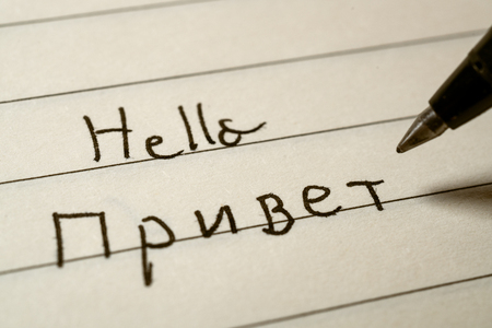 Beginner Russian language learner writing Hello word in Russian cyrillic alphabet on a notebook close-up shot