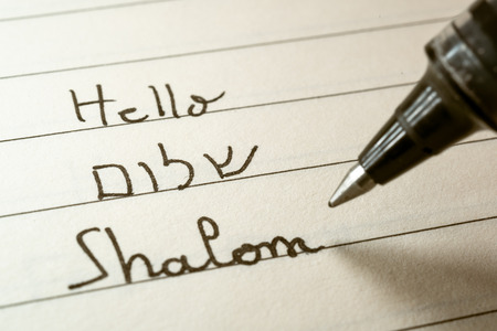 Beginner Hebrew language learner writing Hello Shalom word in Hebrew alphabet on a notebook close-up shot 写真素材