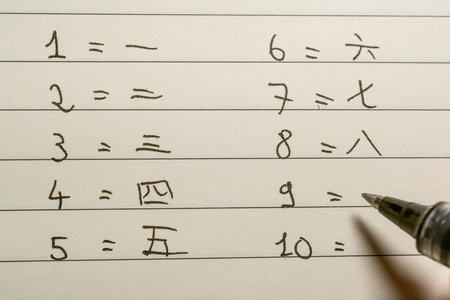 Beginner Chinese language learner writing numbers in Chinese characters on a notebook close-up shot 写真素材 - 123338649