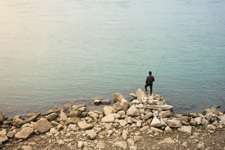 Lonely Asian fisherman standing on rocks in front of beautiful water