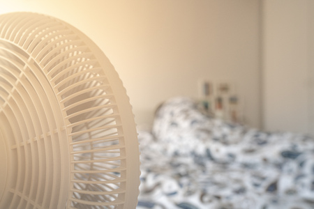Person sleeping in bed with a fan blowing on hot summer day with bright light