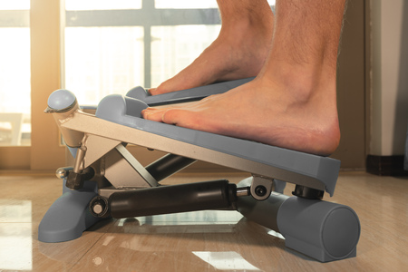 Man doing exercises on steeper barefoot at home