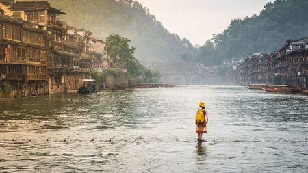 Woman on steeping stones bridge over Tuo Juang river seems walking on water in Fenghuang ancient town in Hunan China