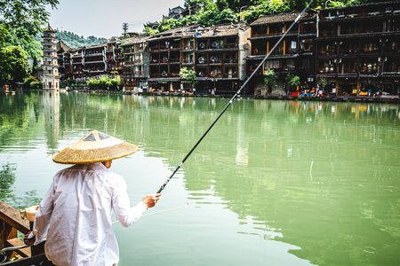 Chinese fisherman wearing an Asian conical hat and scenery of Fenghuang ancient phoenix town in background in Hunan China