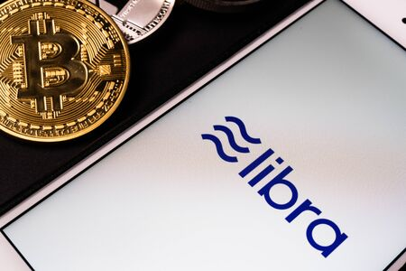 26 June 2019, Wuhan China: Libra the Facebook cryptocurrency logo on mobile phone screen and real coins of other crypto such as Bitcoin next to it