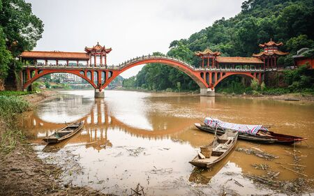 Haoshang arch bridge in oriental Buddha park and small fishing boats on the river in Leshan Sichuan China