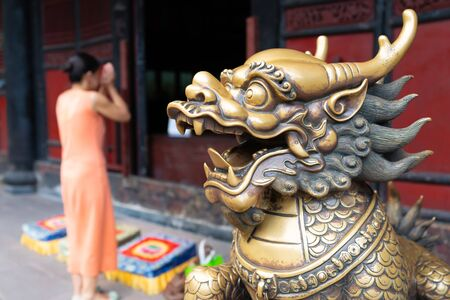 Head of a golden Lion statue at Wenshu monastery and blurred Chinese woman praying joining hands in background in Chengdu Sichuan China