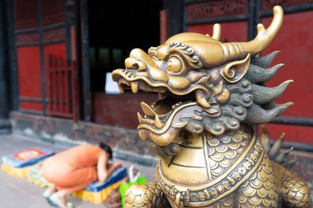 Head of a golden Lion statue at Wenshu monastery and blurred Chinese woman praying kneeling in background in Chengdu Sichuan China