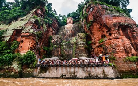 Wide angle view of Leshan Giant Buddha or Dafo from river boat in Leshan Sichuan China