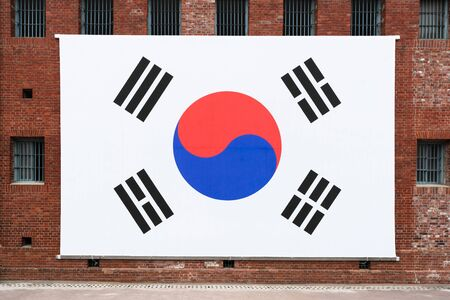 Giant South Korean flag on the red bricks wall of Seodaemun prison hall a former Japanese prison in Seoul South Korea Stok Fotoğraf