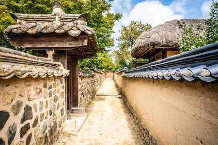 Alley with houses walls and gates in historic Hahoe folk village in Andong South Korea Foto de archivo