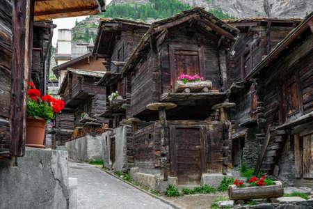 Ancient wooden traditional Swiss raccard granary on stone piles in old Hinterdorf quarter of Zermatt Switzerland
