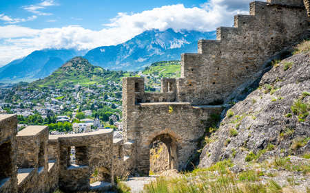 Entrance door and wall of the ruins of Tourbillon castle and Sion hill and city panorama in background in Sion Valais Switzerland
