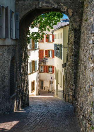 Sion old town vertical view with scenic pedestrian laneway with paved street and medieval arch and buildings in Sion Valais Switzerland