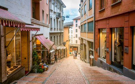 Lugano Switzerland, 1 July 2020: Pedestrian Via Cattedrale sloped shopping street of Lugano with colorful houses in Ticino Switzerland