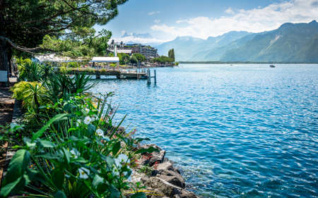 Montreux shoreline with flowers and Lake Geneva view with Alps mountains in background during sunny summer day in Montreux Vaud Switzerland