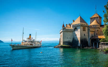 Veytaux Switzerland, 4 July 2020: Montreux touristic steamboat on Lake Geneva and Chillon castle view with clear blue sky in Vaud Switzerland