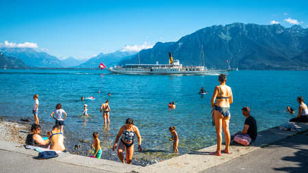 Vevey Switzerland, 4 July 2020: People swimming in Lake Geneva from Vevey beach and touristic steamboat sailing on beautiful water on sunny summer day in Vevey Switzerland 新闻类图片