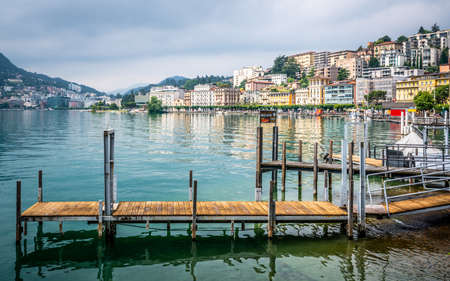 Lugano Switzerland, 1 July 2020: Lugano city panorama and pontoon view on lake shores in Lugano Ticino Switzerland 新闻类图片