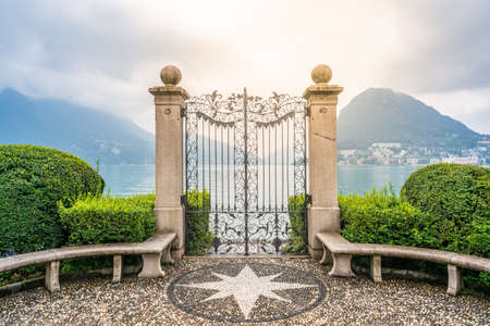 Old wrought-iron gate on Lake Lugano banks in Parco Civico Ciani public garden and dramatic light in Lugano Ticino Switzerland 免版税图像