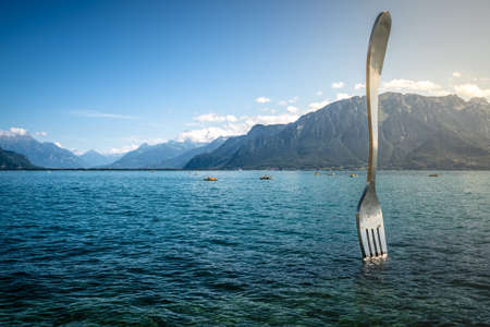 Vevey Switzerland, 4 July 2020: La Fourchette or The Fork the world biggest fork by artist Jean-Pierre Zaugg in middle of Lake Geneva and dramatic light in Vevey Switzerland