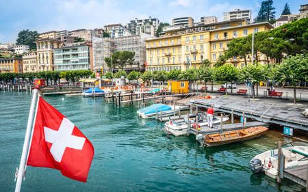 Lugano Switzerland, 1 July 2020: Swiss flag and Lugano cityscape with boats on the shore of Lake Lugano Ticino Switzerland