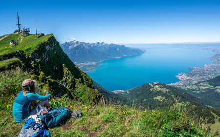 Unrecognizable tourist hiker admiring the aerial view of Lake Geneva from Rochers-de-Naye mountain summit in Vaud Switzerland