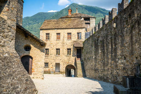 Courtyard and entrance Castello di Montebello castle with building and wall and mountain in background in Bellinzona Ticino Switzerland