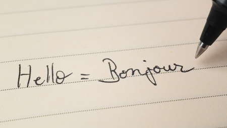Beginner French language learner writing Hello word Bonjour for homework on a notebook macro shot