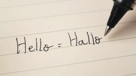 Beginner German or Dutch language learner writing Hello word Hallo for homework on a notebook macro shot 免版税图像